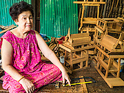 02 NOVEMBER 2016 - BANGKOK, THAILAND:  HONG, 77 years old, the matriarch of the last family making spirit houses in the Ban Fuen community, in her home workshop. There used to be 10 families making traditional spirit houses out of teak wood in Ban Fuen, a community near Wat Suttharam in the Khlong San district of Bangkok. The area has been gentrified and many of the spirit house makers have moved out, their traditional wooden Thai houses replaced by modern apartments. Now there is just one family making the elaborate spirit houses. The spirit houses are made by hand. It takes three days to make a small one and up to three weeks to make a large one. Prices start at about $90 (US) for a small one. The largest, most elaborate ones can cost over $1,000 (US). Almost every home and most commercial buildings in Thailand have a spirit house, which is a shrine to the protective spirit of a the land. Spirit houses are also common in Burma, Cambodia, and Laos.       PHOTO BY JACK KURTZ