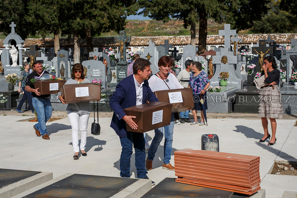 19/05/2018. People carry boxes containing the remains of Tomas or Manuel Escamilla Rebollo, Angel Vinas Diaz and Casto Mercado Molada who were assassinated by dictator Francisco Franco's forces during their burial at the cemetery on May 19, 2018 in Sacedon, Guadalajara province, Spain. General Franco's forces killed Timoteo Mendieta and other people between 1939 and 1940 after Spain's Civil War and buried them in mass graves in Guadalajara's cemetery. Argentinian judge Maria Servini used the international human rights law and ordered the exhumation and investigation of Mendieta's mass grave. The exhumation was carried out by Association for the Recovery of Historical Memory (ARMH) recovering 50 bodies from 2 mass graves and identified 24 of them. Spain's Civil War took the lives of thousands of people on both sides, but Franco continued his executions after the war has finished. Spanish governments has never done anything to help the victims of the Civil War and Franco's dictatorship while there are still thousands of people missing in mass graves around the country. (© Pablo Blazquez)