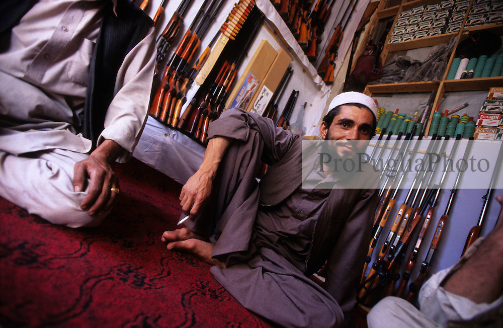 Kabul, 14 August 2005..A local shopkeeper sells Pakistani shotguns and ammunition..