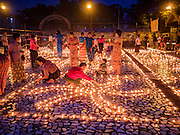 28 OCTOBER 2015 - YANGON, MYANMAR:     People light oil lamps during observances of Thadingyut at Botataung Pagoda in Yangon. Botataung Pagoda was first built by the Mon, a Burmese ethnic minority, around the same time as was Shwedagon Pagoda, over 2500 years ago. The Thadingyut Festival, the Lighting Festival of Myanmar, is held on the full moon day of the Burmese Lunar month of Thadingyut. As a custom, it is held at the end of the Buddhist lent (Vassa). The Thadingyut festival is the celebration to welcome the Buddha's descent from heaven.     PHOTO BY JACK KURTZ