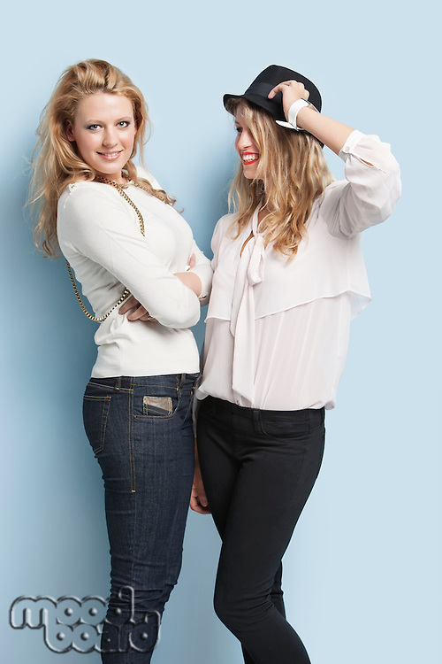 Two happy young women standing together against light blue background
