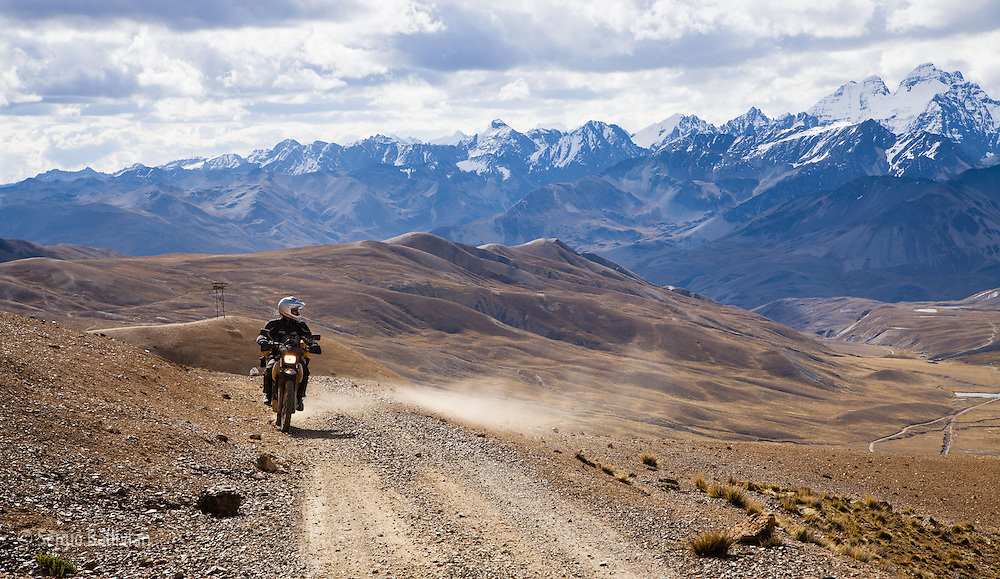 An adventure motorcyclists rides a narrow dirt road in Bolivia's Cordillera Real de los Andes mountain range below Mt. Huayna Potosi (19,985') near La Paz.
