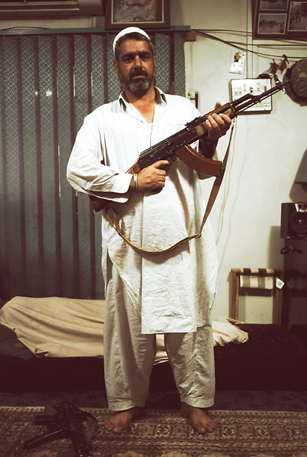 A man poses with a gun at the home of a local drug lord who is responsible for the trafficking of vast quantities of heroine and cocaine within the tribal regions at the Smuggler's Bazaar, Khyber-Pakhtunkhwa, Pakistan on 25th Sep, 2007..
