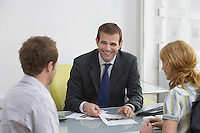 Couple with real estate agent in office