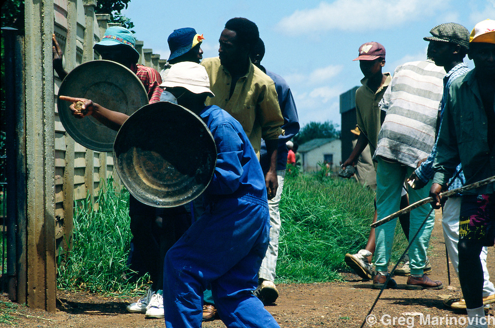 Bekkersdal, Transvaal, South Africa 1994. Azapo supporters try to use dustbin lids to protect themselves from gunfirefrom ANC supporters in clashes between police, army, Azapo and the ANC is Bekkersdal township, 1994.