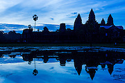 """02 JULY 2013 - ANGKOR WAT, SIEM REAP, SIEM REAP, CAMBODIA:  The west side of Angkor Wat is silhouetted by the rising sun. Angkor Wat is the largest temple complex in the world. The temple was built by the Khmer King Suryavarman II in the early 12th century in Yasodharapura (present-day Angkor), the capital of the Khmer Empire, as his state temple and eventual mausoleum. Angkor Wat was dedicated to Vishnu. It is the best-preserved temple at the site, and has remained a religious centre since its foundation– first Hindu, then Buddhist. The temple is at the top of the high classical style of Khmer architecture. It is a symbol of Cambodia, appearing on the national flag, and it is the country's prime attraction for visitors. The temple is admired for the architecture, the extensive bas-reliefs, and for the numerous devatas adorning its walls. The modern name, Angkor Wat, means """"Temple City"""" or """"City of Temples"""" in Khmer; Angkor, meaning """"city"""" or """"capital city"""", is a vernacular form of the word nokor, which comes from the Sanskrit word nagara. Wat is the Khmer word for """"temple grounds"""", derived from the Pali word """"vatta."""" Prior to this time the temple was known as Preah Pisnulok, after the posthumous title of its founder. It is also the name of complex of temples, which includes Bayon and Preah Khan, in the vicinity. It is by far the most visited tourist attraction in Cambodia. More than half of all tourists to Cambodia visit Angkor.         PHOTO BY JACK KURTZ"""