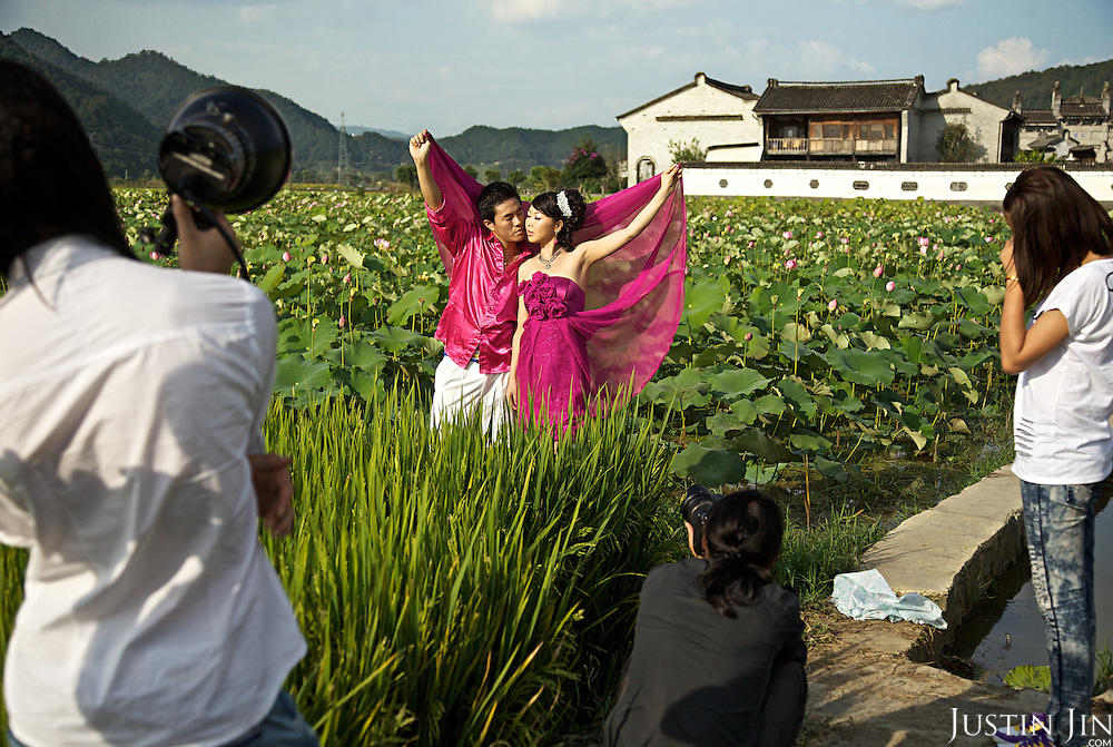 A Chinese couple takes wedding pictures in a lily pond at the Heshun Ancient Town in Tengchong City, Yunnan Province, Southwestern China.
