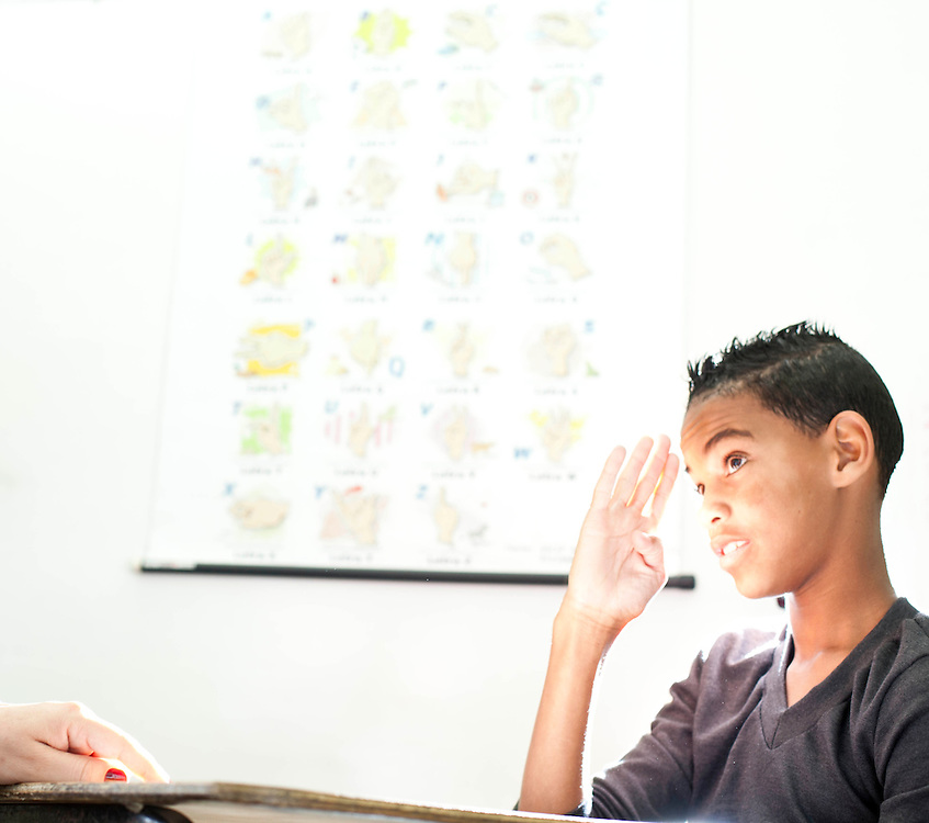 Contagem_MG, Brasil...Aluno atendido no contraturno na sala de recursos para alunos com necessidades especiais. Na foto, ele esta jogando um jogo chamado Pulga Surda, cada casa do tabuleiro pede que ele faca determinado movimento com as maos. A atividade trabalha o condicionamento das maos que e um aspecto fundamental na aprendizagem da lingua de sinais...Student attended the in the resource room for students with special needs. In the photo, he is playing a game called Pulga Surda, in this game He needs to do a particular movement with the hands. The activity works the conditioning of the hands which is a fundamental aspect of learning sign language.. .Foto: LEO DRUMOND / NITRO