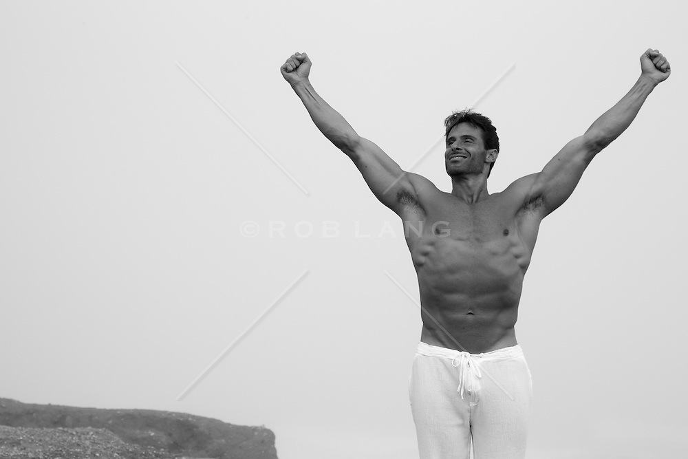 shirtless muscular man with his arms raised in the air in victory