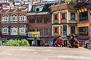 A young monk talks to a friend whilst sitting on the first platform of the Boudhanath stupa in Kathmandu, Nepal.