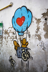Cartoon graffitied on a weathered wall of people in a hot air balloon throwing money bags from the basket, Chinatown, Bangkok, Thailand, Southeast Asia