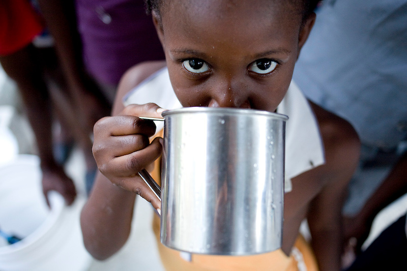 Medjina Morise drinks a cup of water from a filter given by MCC to provide her IDP camp with drinking water. Morise is living her family and 60 other people who are taking refuge in a half built church that survived the earthquake. Nerrette, Haiti. Photo by Ben Depp. 1/27/2010