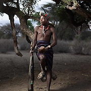 Kore Jagala sits on a tree branch in a dry river bed, Lower Omo Valley, Ethiopia.