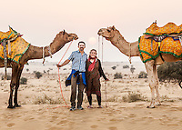 A man and woman holding their camels reigns while posing for a photo in the Thar desert at sunset, Rajasthan, India.