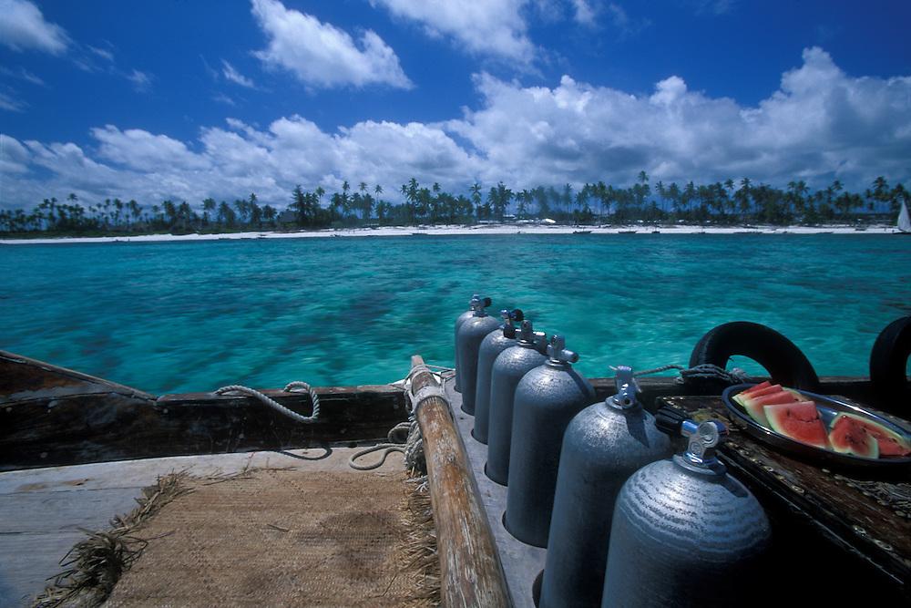 Africa, Tanzania, Zanzibar, Matemwe Bay, Scuba Diving air tanks in a row on charter boat sailing past palm tree lined beach