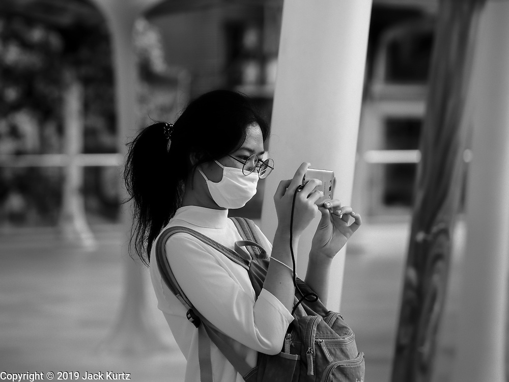 "14 JANUARY 2019 - BANGKOK, THAILAND:      A woman wearing a dust filter breathig mask photographs the Bangkok skyline with her smartphone. Bangkok has been blanketed by heavily polluted air for almost a week. Monday morning, the AQI (Air Quality Index) for Bangkok  was 182, worse than New Delhi, Jakarta, or Beijing. The Saphan Kwai neighborhood of Bangkok recorded an AQI of 370 and the Lat Yao neighborhood recorded an AQI of 403. An AQI above 50 is considered unsafe. Public health officials have warned people to avoid ""unnecessary"" outdoor activities and wear breathing masks to filter out the dust.   PHOTO BY JACK KURTZ"