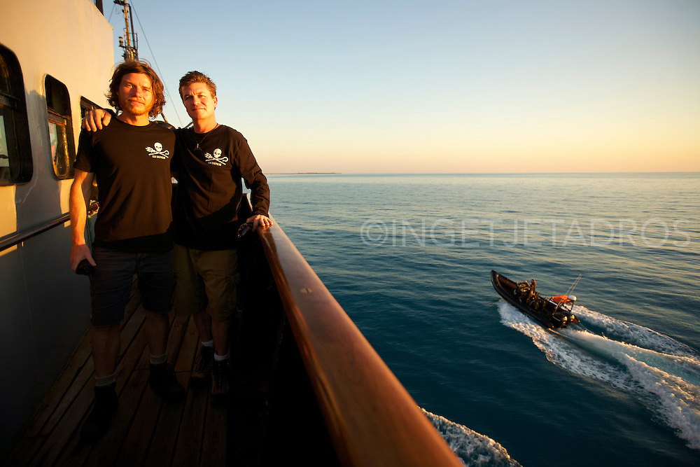 Captain Mal Holland standing on deck with Manager Beck Straussner while an inflatable boat is preparing to pick/drop off VIP's.