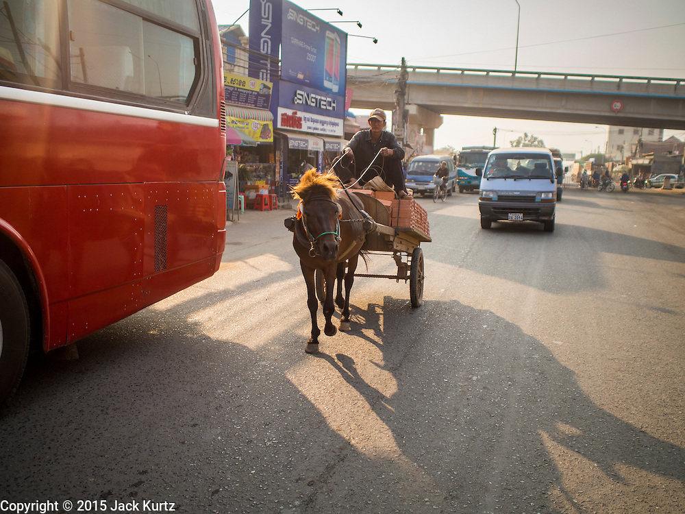26 FEBRUARY 2015 - PHNOM PENH, CAMBODIA: A horse cart is driven up National Road 5 in Phnom Penh. The Prek Pnov Bridge across the Tonle Sap River is in the background.   PHOTO BY JACK KURTZ