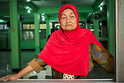 """11 JANUARY 2013 - BANGKOK, THAILAND:   A Muslim woman at a mosque in the Ban Krua neighborhood in Bangkok. The Ban Krua neighborhood of Bangkok is the oldest Muslim community in Bangkok. Ban Krua was originally settled by Cham Muslims from Cambodia and Vietnam who fought on the side of the Thai King Rama I. They were given a royal grant of land east of what was then the Thai capitol at the end of the 18th century in return for their military service. The Cham Muslims were originally weavers and what is known as """"Thai Silk"""" was developed by the people in Ban Krua. Several families in the neighborhood still weave in their homes.                 PHOTO BY JACK KURTZ"""