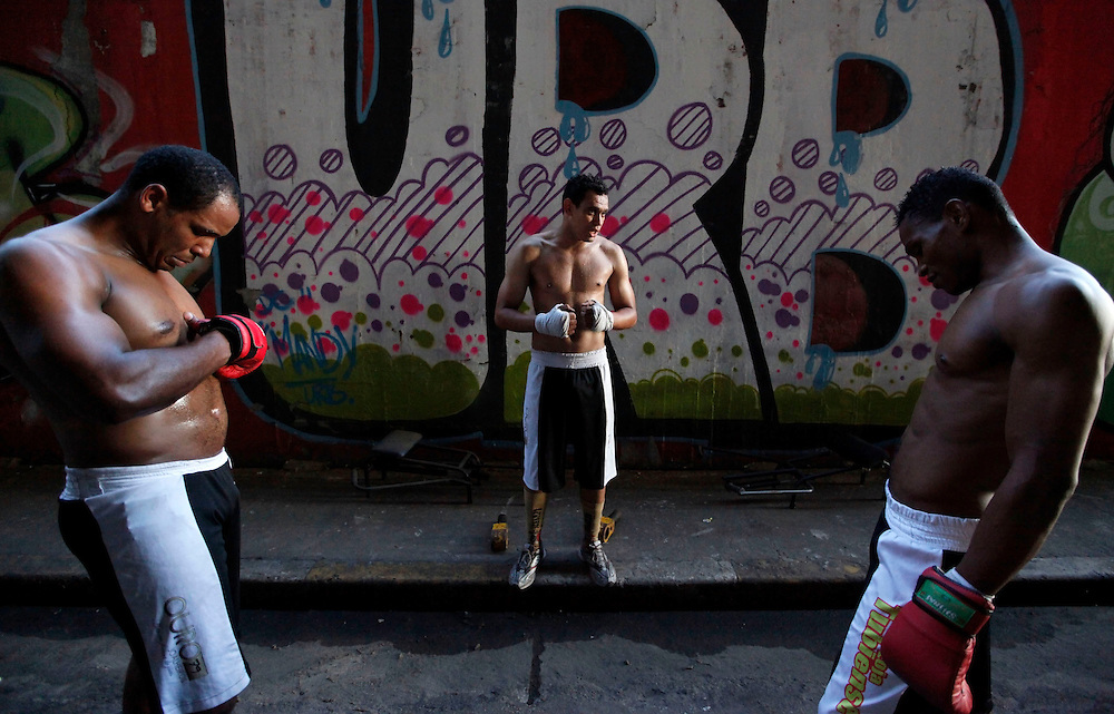 "Aspiring boxers (L-R) Chibata, Joilson Santos (nicknamed ""Talent""), and Valdir Aparecido (nicknamed ""Gorilla""), stand before a training session at a gymnasium under the Alcantara Machado viaduct in the Mooca neighborhood of Sao Paulo, March 25, 2011. The Boxing Academy of Garrido, founded by Brazilian former pro boxer Nilson Garrido, adopts primitive training equipment that he developed himself during his years as a coach, in a project whose goal is to take the sport to the poor and marginalized population."