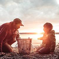 Vater mit Fünfjährigem grillt am Ufer bei Sonnenuntergang, Starnberger See, Oberbayern, Deutschland * Father and little boy barbecueing at sunset, Lake Starnberg, Upper bavaria, Germany