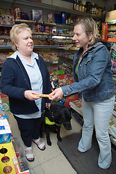 Visually impaired woman in a shop with a guide dog,