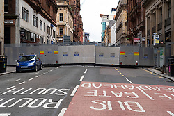 Glasgow, Scotland, UK. 27 June, 2020. Police cordon off city centre street with large steel barrier following stabbing and fatal shooting at Ibis hotel on West George Street yesterday.  Iain Masterton/Alamy Live News