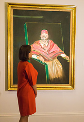"Sotheby's, London, June 19th 2015. International auctioneers Sotheby's gears up to holding what they say is London's highest valued auction of contemporary artworks, to be held on June 24th 2015 where the combined artworks are anticipated to bring in as much as £203 million. PICTURED: A woman admires one of the sale's centerpieces, Francis Bacon's ""Study for Pope I"" With Bacon's works much in demand, this famous monumental work is expected to fetch between £25-35 million.  // Payment/Licencing/Contact details: Paul@pauldaveycreative.co.uk Tel: 07966016296"