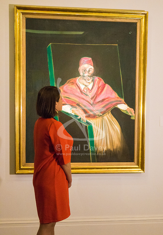 """Sotheby's, London, June 19th 2015. International auctioneers Sotheby's gears up to holding what they say is London's highest valued auction of contemporary artworks, to be held on June 24th 2015 where the combined artworks are anticipated to bring in as much as £203 million. PICTURED: A woman admires one of the sale's centerpieces, Francis Bacon's """"Study for Pope I"""" With Bacon's works much in demand, this famous monumental work is expected to fetch between £25-35 million.  // Payment/Licencing/Contact details: Paul@pauldaveycreative.co.uk Tel: 07966016296"""
