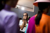 Brazilian fashion designer Dudu Bertholini, of Neon, anxiously checks out his garnets on models backstage at São Paulo Fashion Week for Summer Season 2013/2014, at Bienal, in São Paulo, Brazil, on Wednesday, March 20, 2013.