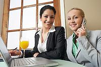 Two business women working in office, portrait