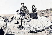 1930s people sitting on a rock in a mountain landscape