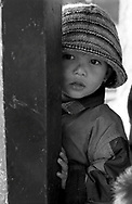 A young boy hides behind the column of an old temple.