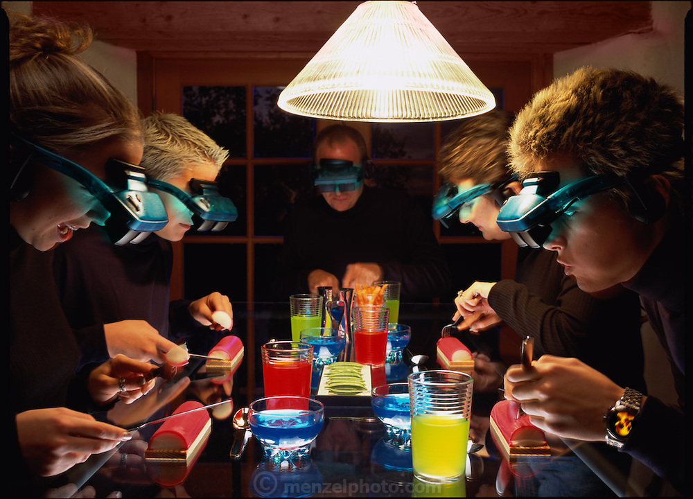 "SUPER SUPPER WITH I-GOGS""  Photo Illustration for the Future of Communication GEO (Germany) Special issue. Fictional Representation and Caption: Statistics and cultural studies always harked that families who dine ""ensemble"" have much better relations than those who do not. The time-honored tradition of families eating together fell by the wayside by the end of the 20th century. In the time-starved 21st century, families re-instituted the practice, but with a twist. They ritualistically eat together but are nearly all multi-tasking at the same time. But they can and often do interact with new half-mirrored goggles ""I-GOGS"" that allow virtually any computer/TV/school/ or video game program to be played at any time. Mealtime became an opportunity to share data as well as food. The Elkins family of Yountville, California are all surfing various audio-visual entertainment nodes while partaking of their Friday evening fish logs, sports drinks and Jello. MODEL RELEASED."