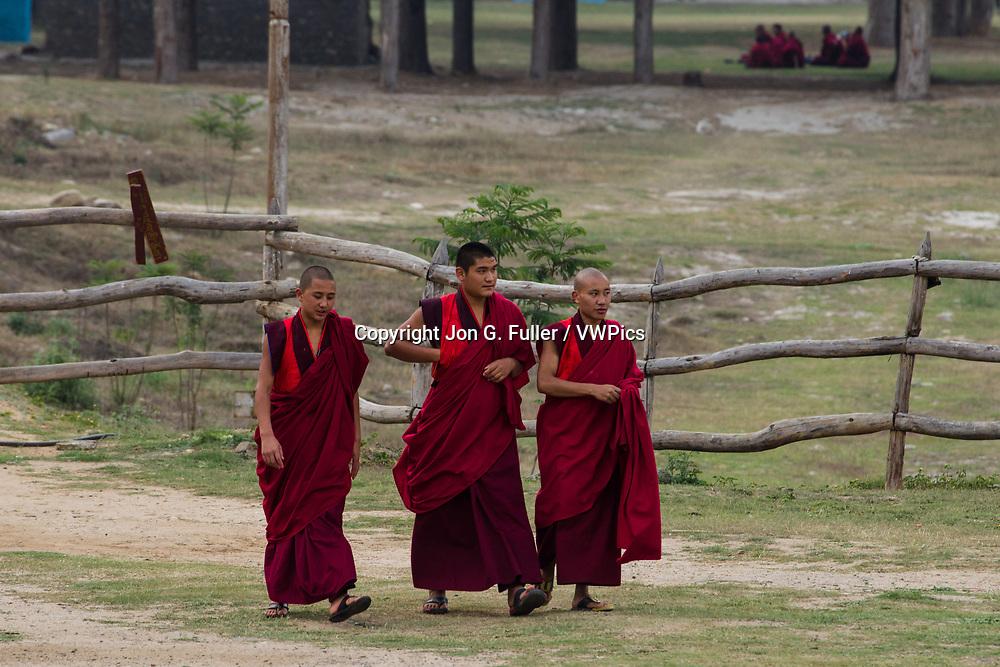 Three Buddhist monks walking to the Punakha Dzong in Punakha, Bhutan.