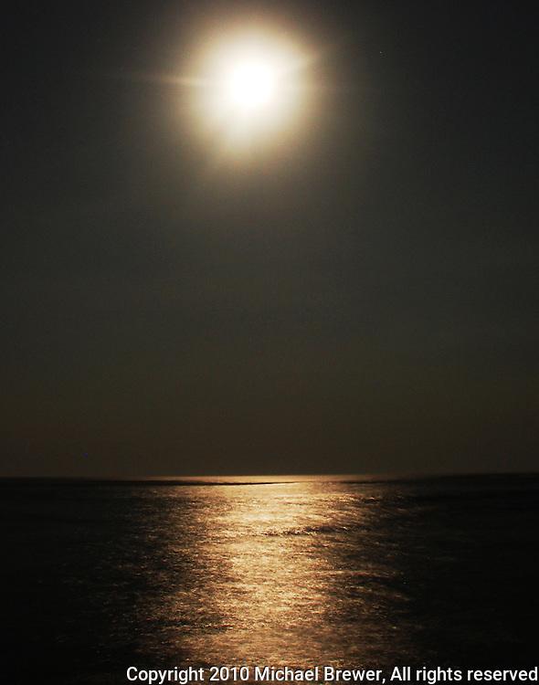 A luminous full moon hangs over the ocean at Sanur Beach in Bali, Indonesia.