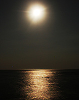 A luminous full moon hangs over the ocean at Sanur Beach in Bali, Indonesia.