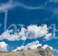 summer hiker in glacier park admires wispy, magical clouds blue sky