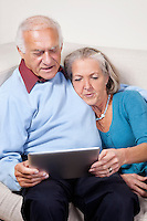 Senior couple using digital tablet at home