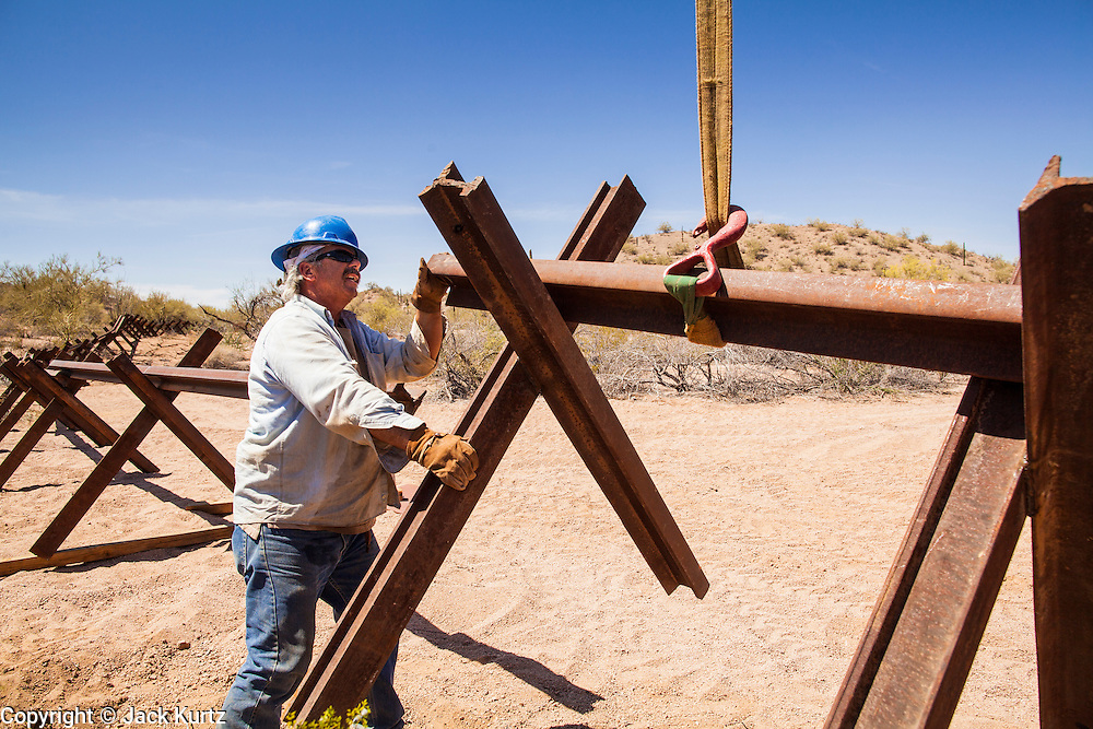 """03 MAY 2012 - VEKOL VALLEY, RURAL PINAL COUNTY, AZ:   James Peters (CQ), from the BLM office in Safford, works on the installation of vehicle barriers on Bureau of Land Management land south of Interstate 8 and west of Casa Grande in rural Pinal County. The area has been a hotbed of illegal immigrant and drug smuggling for years. The BLM has undertaken a series of """"surges"""" in the area, increasing their law enforcement patrols and partnering with Border Patrol and Pinal County Sheriff's Department officers to reduce criminal activity in the area.        PHOTO BY JACK KURTZ"""