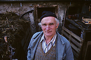 Dressed in typical overalls for the area, traditional Alpine farmer Peter Eberle stands looking up at the viewer for a portrait in the courtyard of his dairy farm in Balzers, Liechtenstein. Mr Eberle wears a woolen hat and blue workman's overalls. He looks a proud but tired and weathered gentleman in his latter years and appears to be an experienced Alpine farmer and we can see a heap of manure over his shoulder and an old fashioned scythe for mowing long grass, leaning against a barn wall. Liechtenstein is a landlocked Principality bordered by the Alpine countries of Austria and Switzerland and is a winter sports resort, though best known as a tax haven, attracting companies worldwide to register their assets in complete secrecy. Its agricultural output is mainly wheat, barley, corn, potatoes, livestock and dairy products though technology companies have been eroding the traditional ways of life such as Peter's for decades.