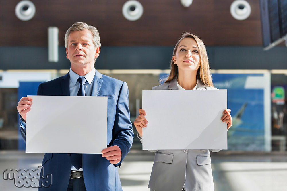 Business people standing while holding blank white placard in arrival area at airport
