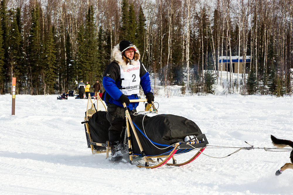 Musher Martin Buser competing in the 41st Iditarod Trail Sled Dog Race on Long Lake after leaving the Willow Lake area at the restart in Southcentral Alaska.  Afternoon.