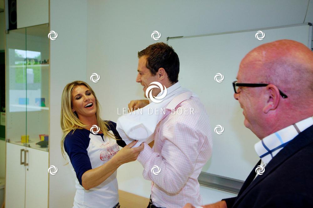 HILVERSUM - Rugby Academy MiddenOost presenteertde haar nieuwe ambassadeurs op het Comenius College. Met op de foto  Ries Fok overhandigden de nieuwe t-shirts van Macron-vandergijp aan Daniëlle Oerlemans-Overgaag en Tim Visser. FOTO LEVIN DEN BOER - PERSFOTO.NU