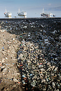 Black sand beach covered in plastic trash and other pollution in Ende, Flores, Indonesia