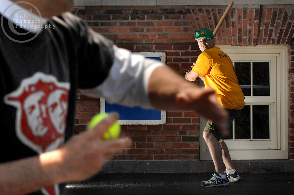 "Andy Ettinger, 49 and an independent bookseller, pitches to Alan Fine, also 49 and a screenplay writer, during a game of stickball..---.The Ethical Stickball League has been operating since 1970, meeting every Sunday in the parking lot behind Hastings High School from 10:30AM to 1PM.  The players are men now mostly in their 70s - carrying nicknames like ""The Wise One"", ""Hit Man"" and ""Plays Hurt"" - who have an affiliation with the school, either as former teachers, students or neighbors. As their slogan suggests, all it takes for a few hours of ""Aestas Aeterna"" (Eternal Summer) is an outside temperature above 45 degrees and 8 willing souls...CREDIT: Rob Bennett for The NY Times"