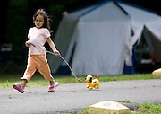 SOUTHBURY, CT- 06 JULY 2008- 070608JT01-.Isabella Lucas, 5, of Bridgeport, walks her toy dog Spot, which she's had since she was one-year-old, around a camping area at Kettletown State Park in Southbury on Sunday. Lucas' mother, Valerie, said she has camped at Kettletown every summer with her family for 30 years..Josalee Thrift / Republican-American