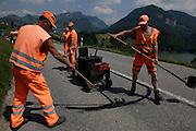 Ouvriers des ponts et chaussées en habit de sécurité en train de réparer la route avec du goudron liquide