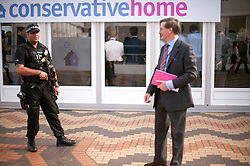 © Licensed to London News Pictures. 30/09/2014. Birmingham, UK. Dominic Grieve watches and armed police officer at the conference.  The Conservative Party Conference in Birmingham 30th September 2014. Photo credit : Stephen Simpson/LNP