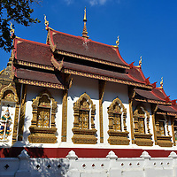 Ho Trai Library at Wat Hua Kuang in Chiang Mai, Thailand <br /> Buddhist temples in Thailand usually have a ho trai that house the holy Tripitaka scriptures.  Typically these libraries are very elaborate and this one at Wat Hua Kuang is an excellent example.  The hornlike finials above the two-tiered red roof are called chofas which represent the garuda.  Also notice the ornate, gilded windows and the ceramic relief of a Yaksha demon holding a sword.
